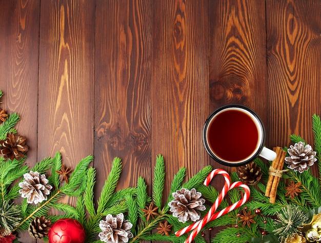 Weihnachts- und guten rutsch ins neue jahr-hintergrund mit tee. draufsicht, kopienraum, braunes dunkles hölzernes
