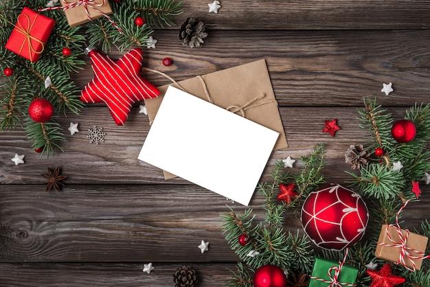 Weihnachts- und happy new year-grußkarte mit tannenzweigen, geschenkboxen, roten feiertagsdekorationen auf rustikalem holztisch. attrappe, lehrmodell, simulation. draufsicht mit kopienraum