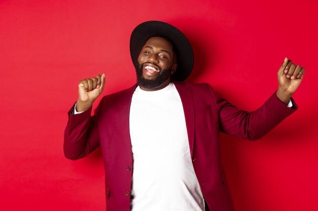 Weihnachts- und menschenkonzept. fröhlicher schwarzer mann, der neujahr feiert und tanzt, party-outfit trägt, roter hintergrund