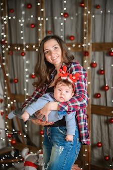 Weihnachts- und mutterkonzept. weihnachts- und personenkonzept - mutter und baby mit geschenken. auf einem weihnachtshintergrund. warmes weihnachten.