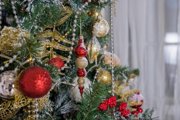 Weihnachts- und neujahrsdekoration. winterurlaubkunstdesign mit feiertagsflitter. schöne weihnachtsbaumnahaufnahme verziert mit goldstern, stechpalmenbeere, lametta. geschmückter weihnachtsbaum.