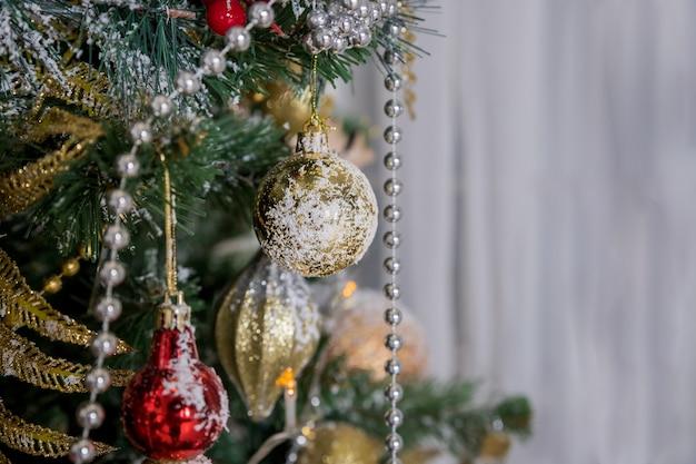 Weihnachts- und neujahrsdekoration. winterurlaubkunstdesign mit feiertagsflitter. schöne weihnachtsbaumnahaufnahme verziert mit goldstern, stechpalmenbeere, lametta.