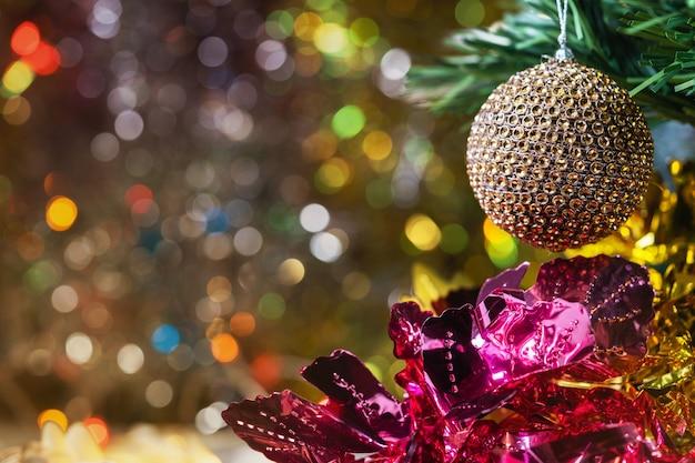 Weihnachts- und neujahrsdekorationen und beleuchtung mit einer großen goldenen kugel im vordergrund.