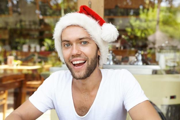 Weihnachts- und neujahrsfeier. innenporträt des glücklichen attraktiven jungen kaukasischen mannes mit bart, der am café aufwirft, das roten weihnachtsmannhut trägt und fröhlich lacht, während urlaub genießt