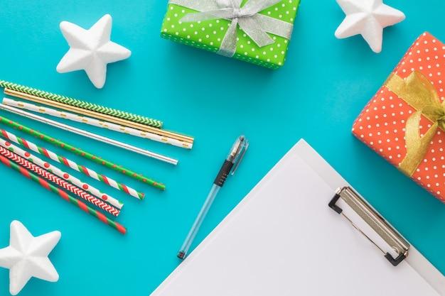 Weihnachts- und neujahrsfeiertag, zum der liste mit notizblock, stift, geschenkboxen, cocktailgefäßen, sternen zu tun