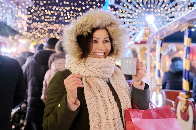 Weihnachts- und neujahrsfeiertage, glückliche reife schöne frau mit einkaufstüten und tasse heißem getränk am weihnachtsmarkt