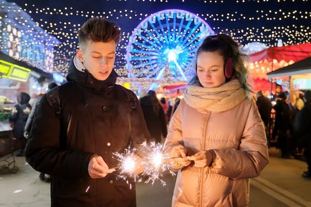 Weihnachts- und neujahrsfeiertage, glückliches teenagerpaar mit wunderkerzen, die am weihnachtsmarkt feiern und spaß haben