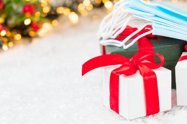 Weihnachts- und neujahrsgeschenke und gesichtsmaske unter geschmücktem weihnachtsbaum