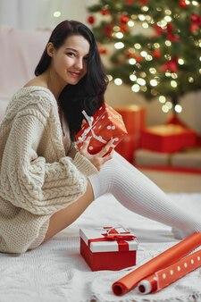 Weihnachts- und neujahrsgeschenkverpackung von frau zu hause während der winterferien