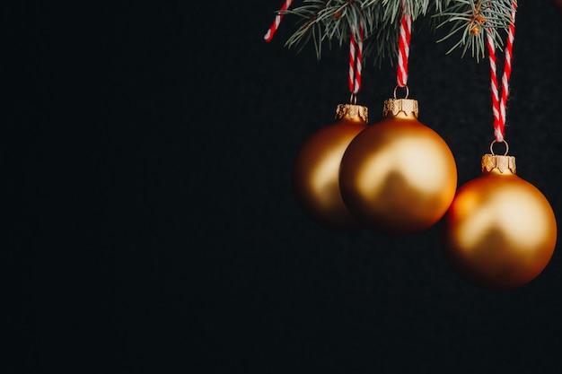 Weihnachts- und neujahrsgutschein. zweige der tanne und dekoration mit goldenen kugeln mit rotem faden auf einem schwarzen hintergrund isoliert