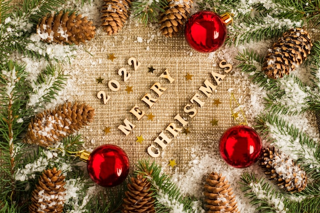 Weihnachts- und neujahrshintergrund auf sackleinen mit den zahlen des kommenden jahres, fichtenzweige, kegel und spielzeug, rote kugeln. ansicht von oben.