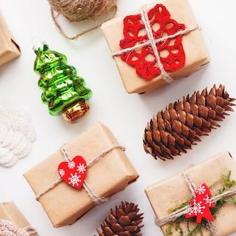 Weihnachts- und neujahrshintergrund mit den handgemachten geschenken eingewickelt im kraftpapier und in den dekorationen.
