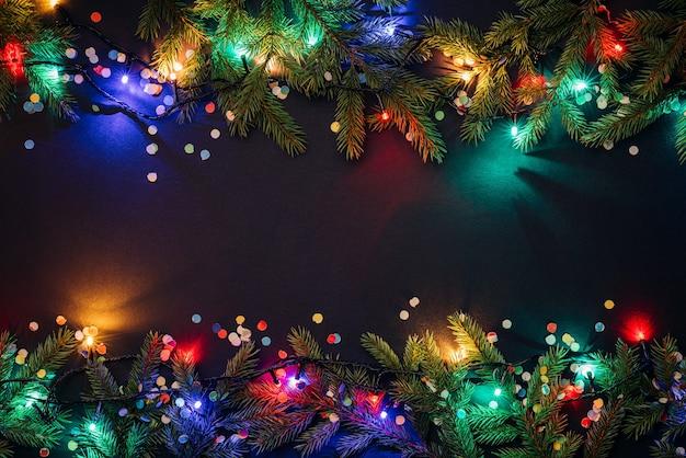 Weihnachts- und neujahrshintergrund mit kopienraum für text. lichterketten und dekor aus tannenzweigen und konfetti. flache lage, ansicht von oben