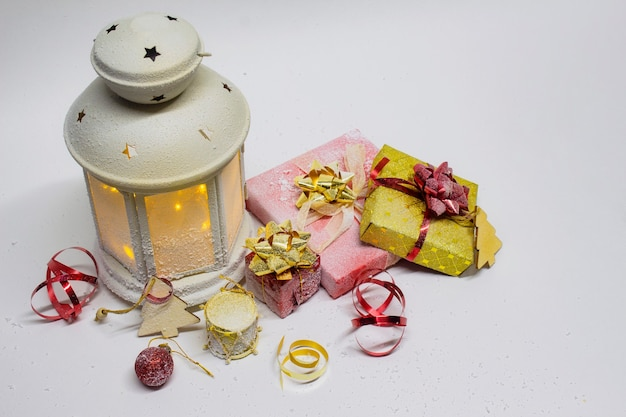 Weihnachts- und neujahrskomposition. festlich leuchtende laterne mit dekorationen, geschenken und hellen schleifen auf weißem hintergrund.