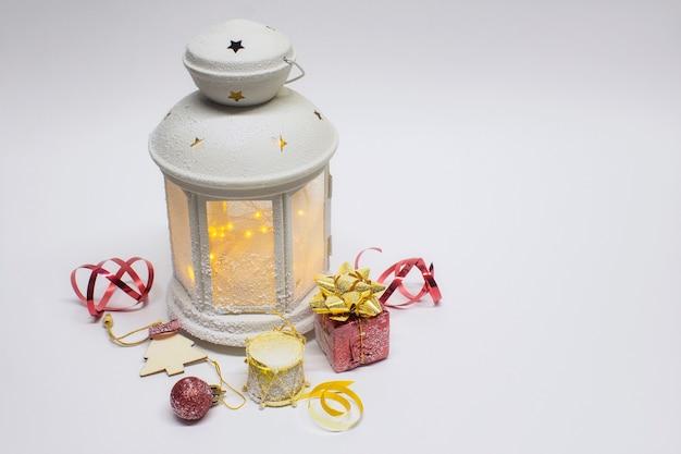 Weihnachts- und neujahrskomposition. festlich leuchtende laterne mit dekorationen, geschenken und hellen schleifen