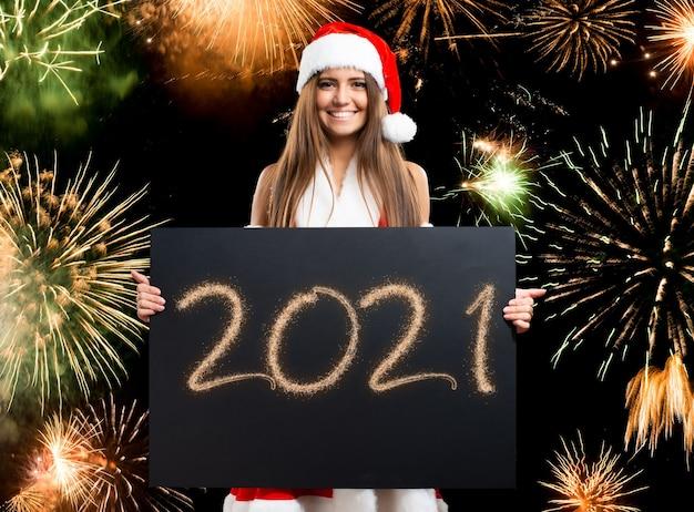Weihnachts- und neujahrskonzept, frau, die eine glückliche 2021 wünscht karte