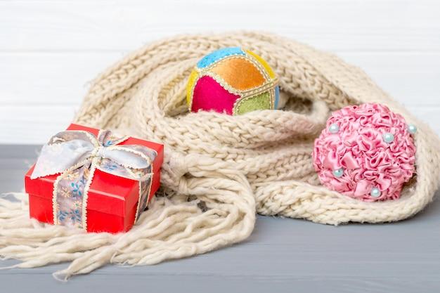 Weihnachts- und neujahrskugeln und geschenkbox im winterstrickschal