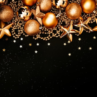 Weihnachts- und neujahrsrahmen mit kopierraum. goldene kugeln und sterne auf schwarzem quadratischem hintergrund.