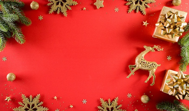 Weihnachts- und neujahrswandkonzept. draufsicht auf weihnachtsgeschenkbox, fichtenzweige, tannenzapfen, rentier, weihnachtsball und schneeflocke auf roter wand.