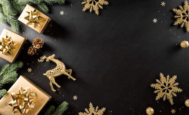 Weihnachts- und neujahrswandkonzept. draufsicht auf weihnachtsgeschenkbox, fichtenzweige, tannenzapfen, rentier, weihnachtskugel und schneeflocke auf schwarzer holzwand.