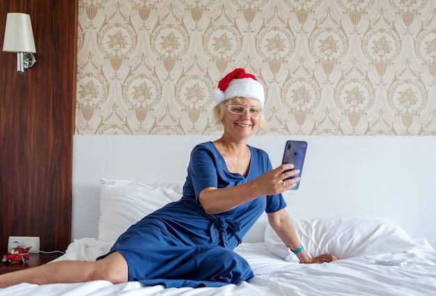 Weihnachts-, weihnachts-, online-grußkonzept - eine frau in einem weihnachtsmann-helferhut mit einem smartphone.