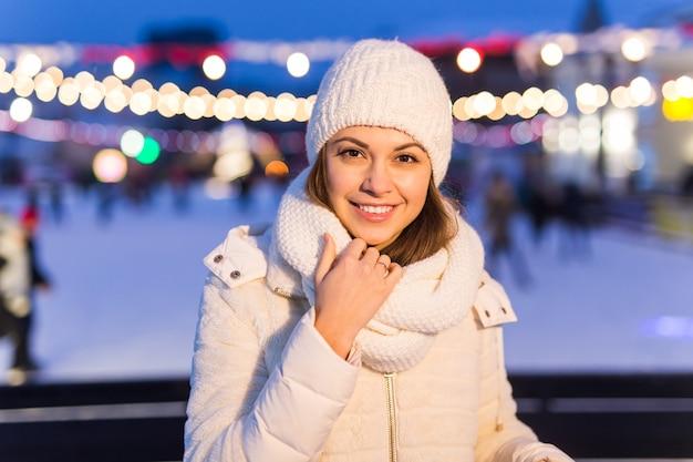Weihnachts-, winter-, technologie- und freizeitkonzept - glückliche junge frau, die mit smartphone auf der eisbahn fotografiert.