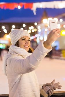 Weihnachts-, winter-, technologie- und freizeitkonzept - glückliche junge frau, die mit smartphone auf der eisbahn im freien fotografiert.