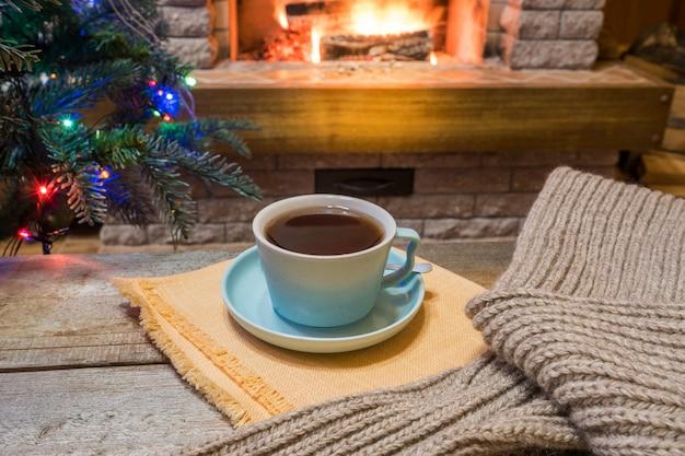 Weihnachtsabend. gemütlicher kamin und eine tasse tee auf holztisch, warmer schal.