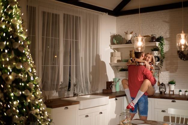 Weihnachtsabend in der küche. junge leute küssen und umarmen sich.