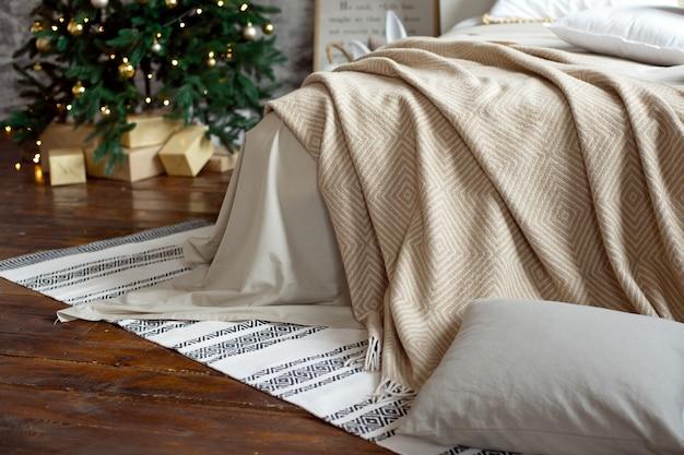 Weihnachtsapartmentdekor, skandinavische gemütliche wohnkultur, bett mit warmen strickdecken neben dem weihnachtsbaum. lichter und girlanden.