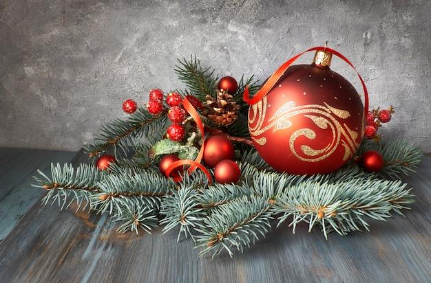Weihnachtsarrangement mit kugeln, tannenzweigen und gefrosteten beeren auf rustikalem holz