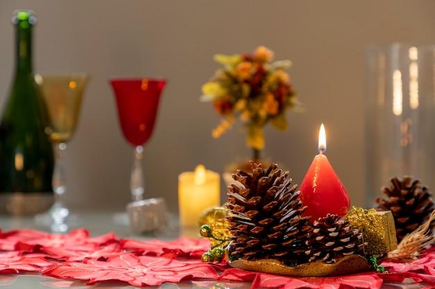Weihnachtsarrangement mit tannenzapfen und brennenden kerzen und unscharfem hintergrund
