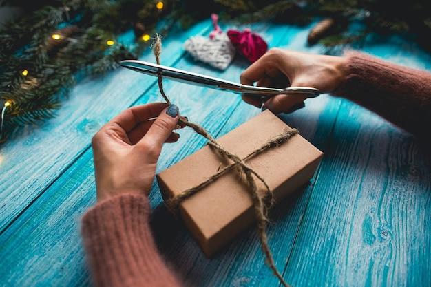 Weihnachtsartikel auf einem blauen holztisch. die hände der frau, die weihnachtsgeschenk einwickeln.