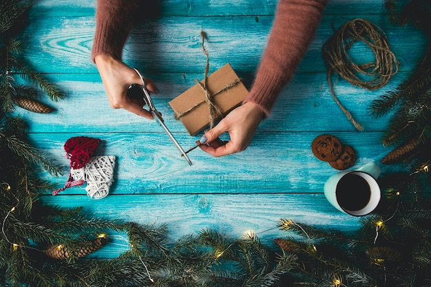 Weihnachtsartikel auf einem blauen wodden tisch. die hände der frau, die weihnachtsgeschenk einwickeln.