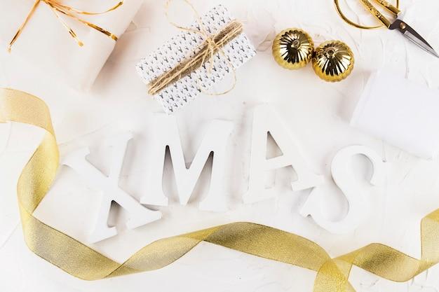 Weihnachtsaufschrift mit geschenkboxen und kugeln