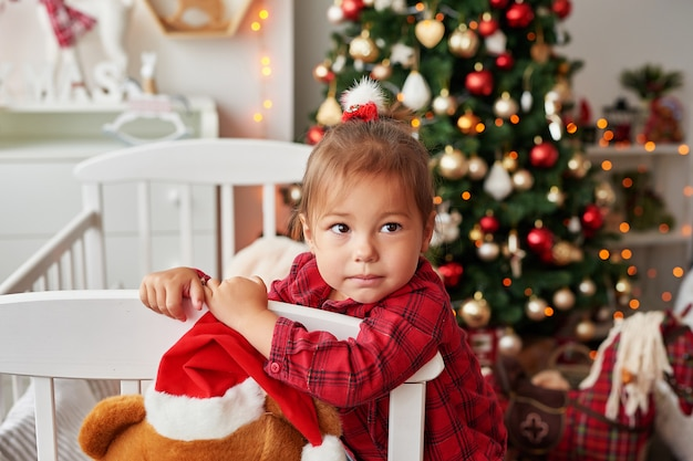 Weihnachtsbaby. kleines lächelndes mädchen im weißen bett im kinderzimmer