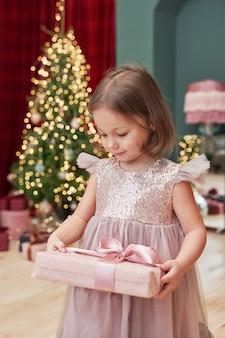 Weihnachtsbaby mit geschenken nahe des weihnachtsbaumes