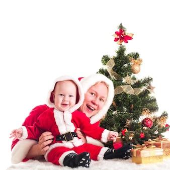 Weihnachtsbaby und mama unter dem tannenbaum isoliert