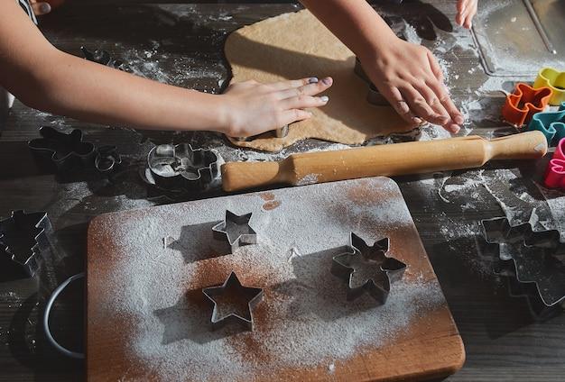 Weihnachtsbacken. ingwerteig für lebkuchen, lebkuchenmänner. neujahrstraditionen konzept und kochprozess. kekse auf dunkelbraunem holztisch. familie, die lebkuchen macht