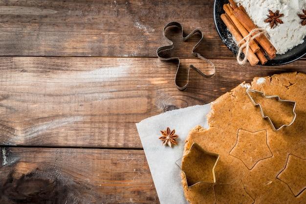 Weihnachtsbacken ingwerteig für lebkuchenlebkuchenmannsterne weihnachtsbaum-nudelholzgewürzmehl (zimt und anis) auf dem hauptküchenholztisch