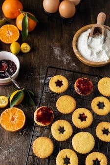 Weihnachtsbacken, traditionelle linzer kekse mit orangen- und beerenmarmelade auf holztisch