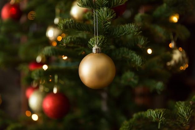 Weihnachtsbälle auf weihnachtsbaum, großes licht mit bokeh mit schatten von der niederlassung.