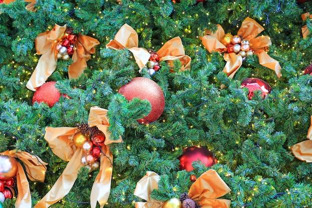 Weihnachtsbälle und -licht, die an den kieferniederlassungen hängen. weihnachten winter hintergrund.