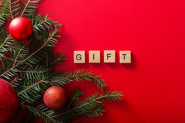 Weihnachtsbäume mit roten kugeln und dem wort geschenk aus holzbuchstaben o