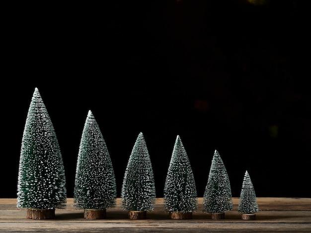 Weihnachtsbäume mit schnee auf holztisch gegen dunklen hintergrund, platz für text