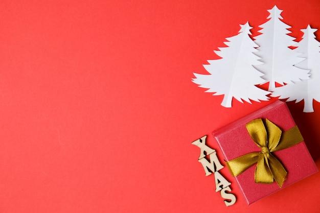 Weihnachtsbäume schnitten vom papier mit aufschrift weihnachten in den hölzernen buchstaben und im geschenk