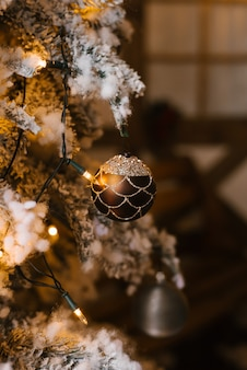 Weihnachtsball auf dem weihnachtsbaum mit glühenden lichtern