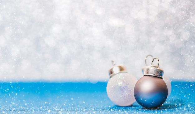 Weihnachtsball auf klarem blauem funkelnboden und weißer bokeh unschärfewand mit schneeflocke falli