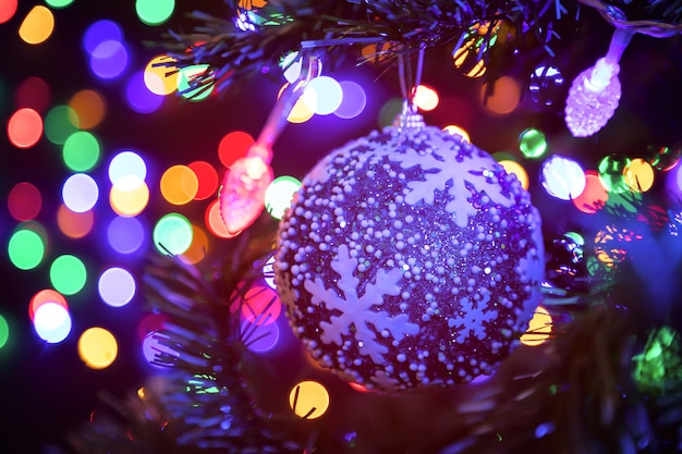 Weihnachtsball, der an einem weihnachtsbaum im hintergrund viele girlanden glühen in verschiedene farben hängt konzept des neuen jahres und des weihnachten.