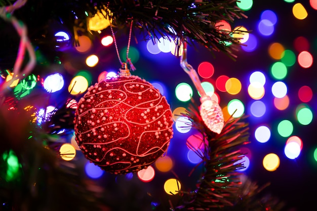 Weihnachtsball, der an einem weihnachtsbaum im hintergrund viele girlanden glühen in verschiedene farben hängt.